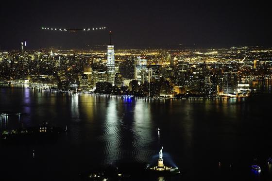 Das Solarflugzeug Solar Impulse 2 beim Flug über New York mit Kurs auf die Freiheitsstatue.