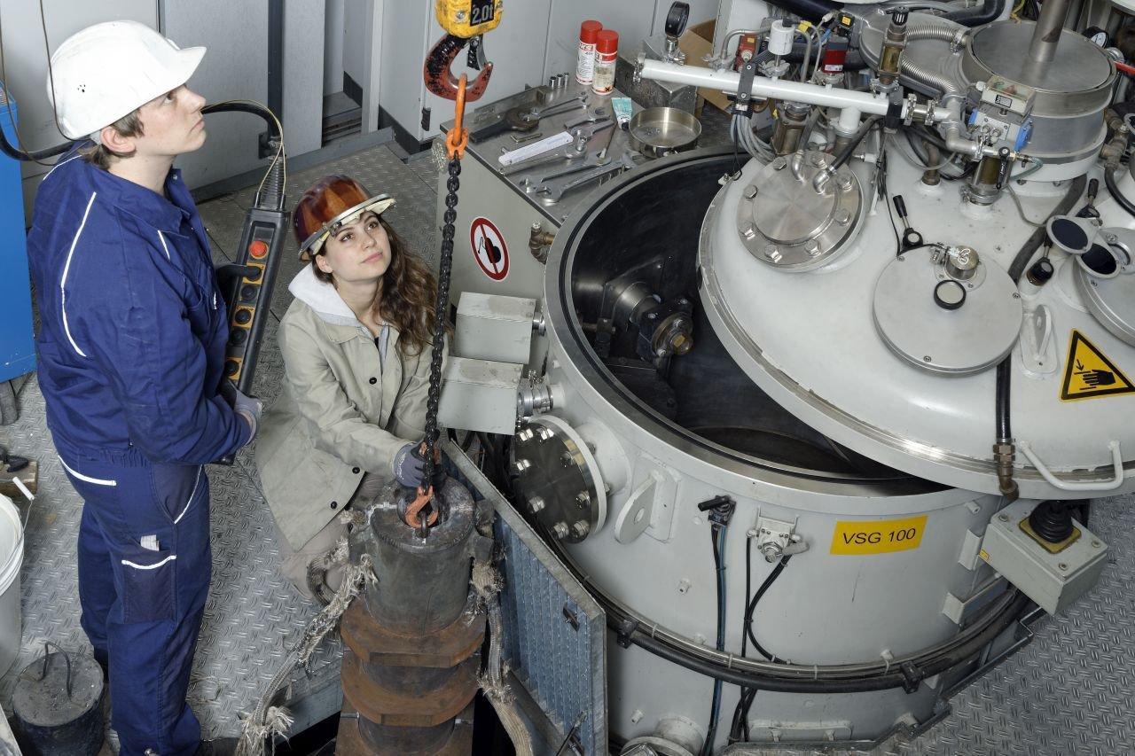 Die IME-Forscher Janik Brenk und Lilian Peters entnehmen eine Kokille, also eine wiederverwendbare Form zum Gießen, die mit einer Titanlegierung gefüllt ist.