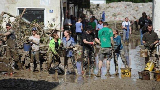 Helfer befreien am 04. Juni 2016 ein vom Hochwasser betroffenes Haus in Simbach am Inn (Bayern) mit Eimern vom Schlamm. Die Flutwelle verursachte mehr als eine Milliarde Euro Schaden. Chemnitzer Forscher<strong></strong>haben jetzt eine textile Membran entwickelt, die das Wasser wirksam aufhält und die Kräfte ableitet.