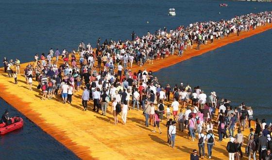 """In Norditalien können Menschen derzeit übers Wasser gehen. Noch bis zum 3. Juli ist am See Iseo die Installation """"Floating Piers"""" des Verpackungskkünstlers Christo zu sehen."""