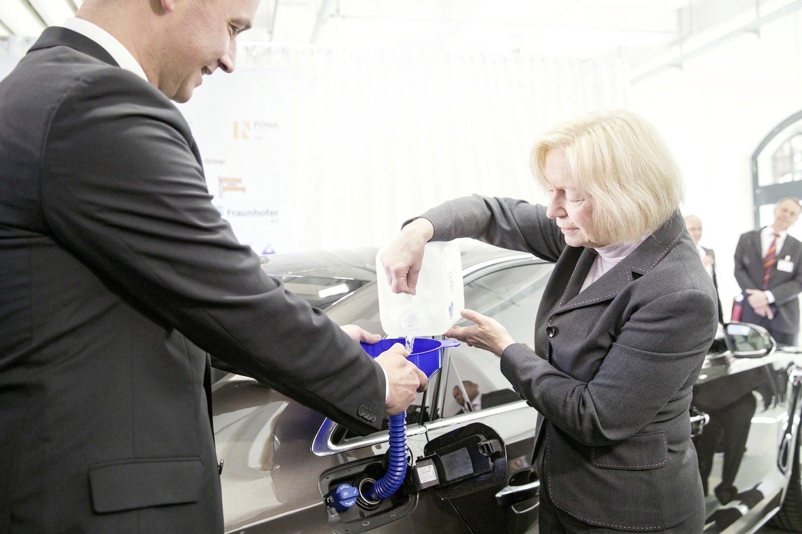 Forschungsministerin Johanna Wanka befüllt bei einem PR-Termin ihren Dienstwagen mit den ersten fünf Liter Audi e-diesel. Neben ihr steht Reiner Mangold, der bei Audi die nachhaltige Produktentwicklung leitet.