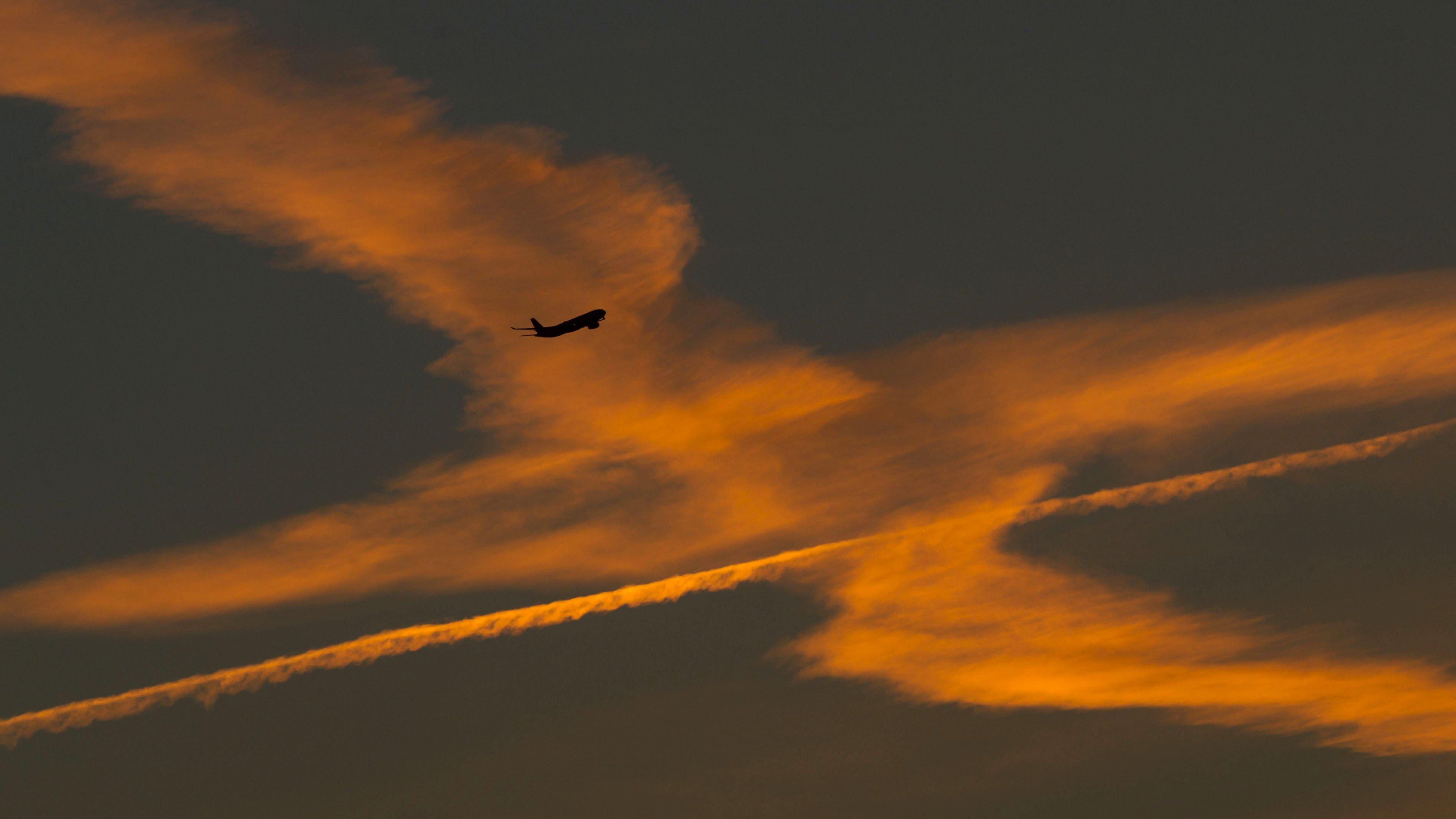 Ein Flugzeug im Anflug auf den Flughafen von Frankfurt am Main (Hessen) passiert Kondensstreifen von vorhergehenden Maschinen, die von der aufgehenden Sonne orange beleuchtet werden.