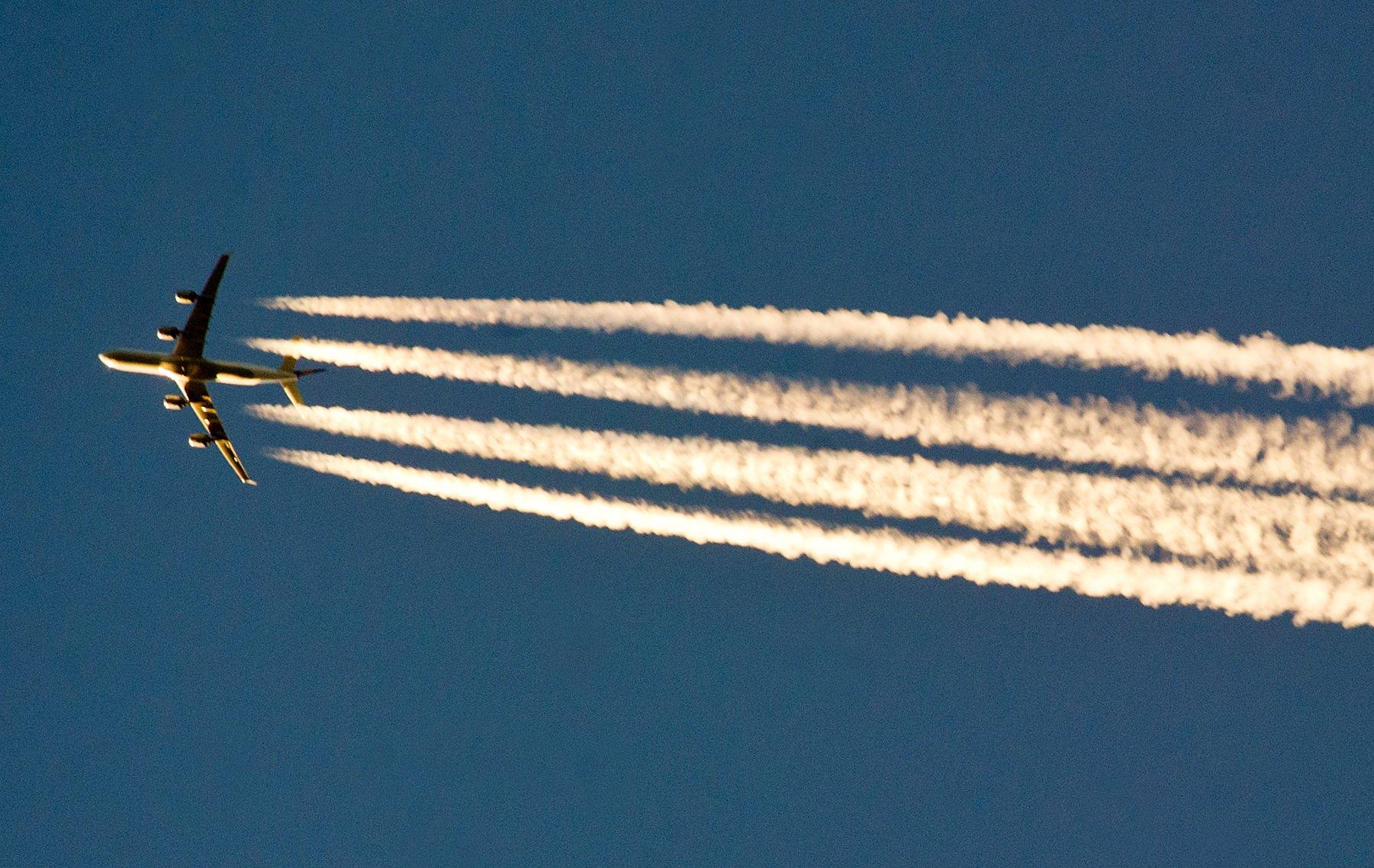 Ein Flugzeug hinterlässt Kondensstreifen am Himmel. Sie entstehen, wenn heiße, wasserdampfhaltige Triebwerksabgase von Luftfahrzeugen auf kalte Luft treffen.