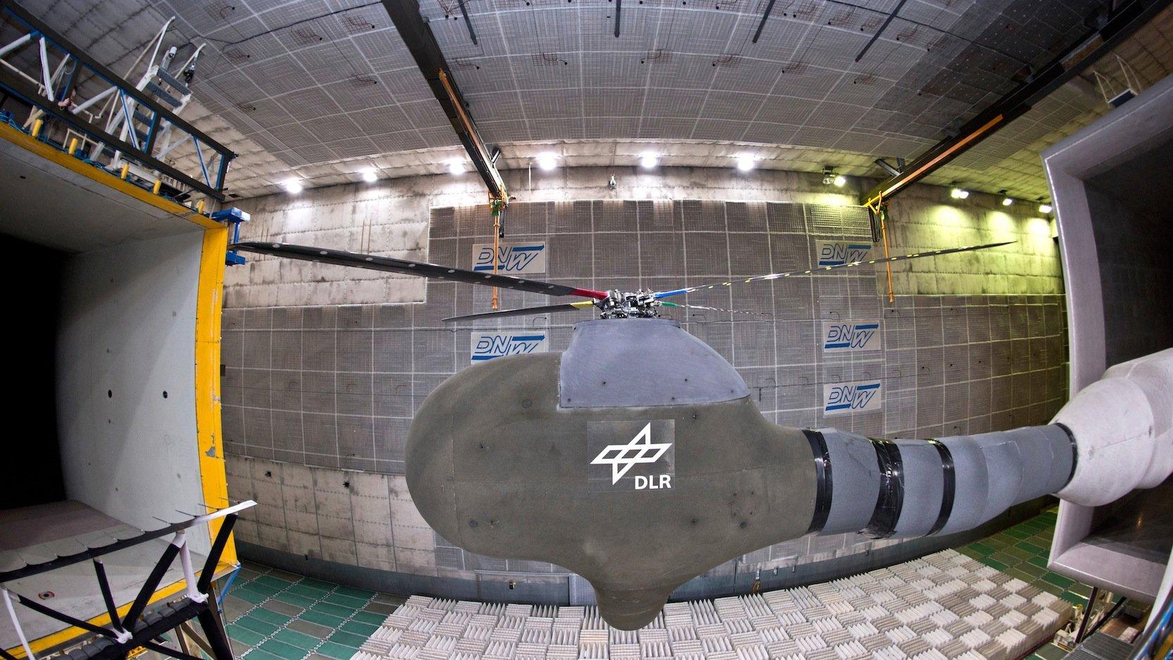 Windkanal mit einem vom DLR entwickelten Versuchsaufbau für Hubschrauberrotoren: Die neuartige Antriebstechnik macht die Rotoren nicht nur leiser, sondern reduziert auch die unangenehmen Vibrationen im Hubschrauber.