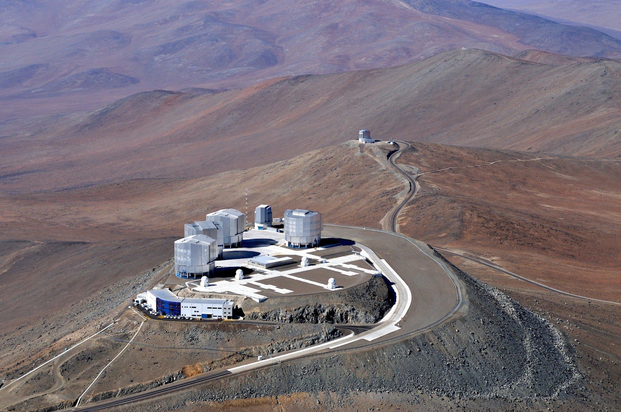 Das Very Large Telescope (VLT) der ESO auf dem Paranal liegt in derdünn besiedelten Atacamawüste im Norden Chiles. Sie gilt als trockenste Wüste der Erde. Links neben dem Teleskop sind auch weitereGebäude wie das Kontrollzentrum am vorderen Rand der Plattform zu erkennen.