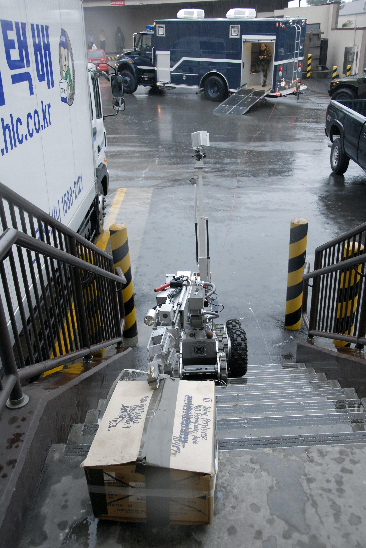 Übung der US Air Force auf der Osan Air Base in Südkorea: Ein Roboter Andros F6A vonNorthrop Grumman Remotec birgt ein gefährliches Paket, das auf einer Treppe abgelegt ist.