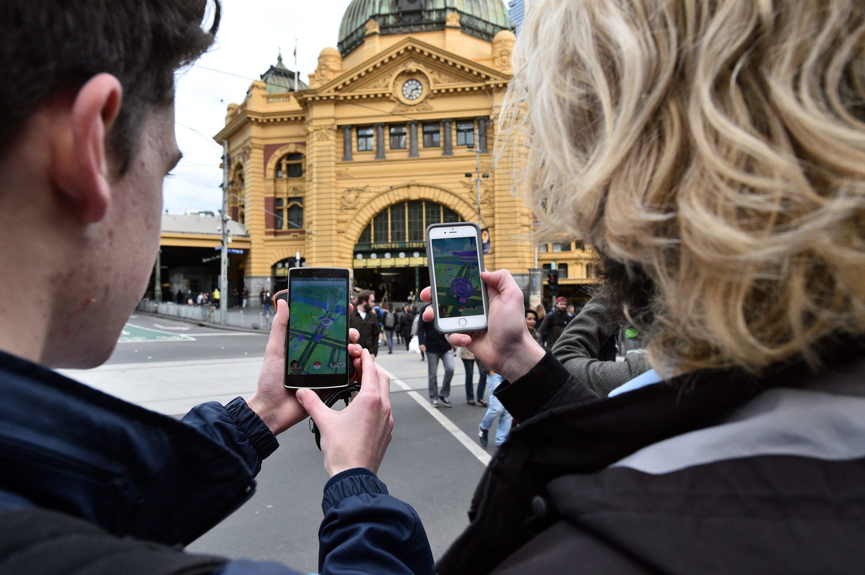 Das Smartphone-Game verbreitet sich rasend schnell rund um den Globus: Zwei Studenten spielen in Australien Pokémon Go auf der Flinders Street in Melbourne.