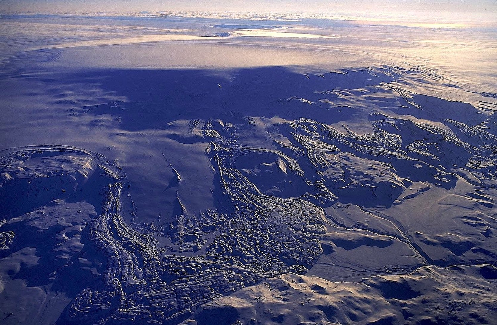 Das ist der vom größten Gletscher Europas bedeckte VulkanBárdarbunga, fotografiert im Jahr 1996. Deutlich zu erkennen ist die so genannte Caldera. Diese Einbuchtung ist in ihrer längsten Ausdehnung 11 km lang. Die Caldera senkte sich bei der Eruption 2014 um 65 m.