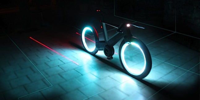 Cyclotron Bike im Dunkeln mit roten Laserstreifen rechts und links um das Hinterrad