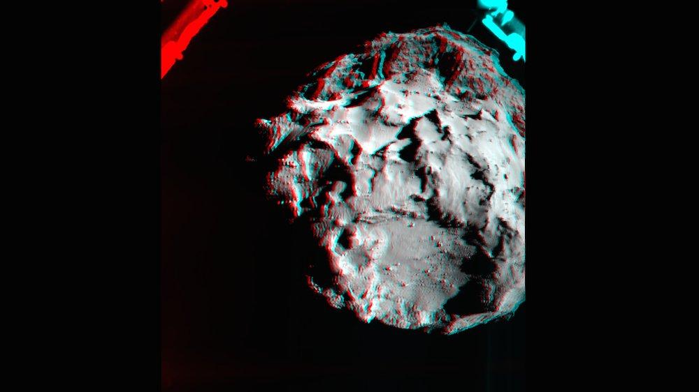 Dieses Stereobild zeigt den Kometen Churyumov-Gerasimenko in 3D. Aufgenommen wurde es während des Abstiegs des Landers Philae mit der ROLIS-Kamera, die an der Unterseite des Landers sitzt. Verwendet wurden zwei Fotos, die um 15.38 Uhr MEZ sowie zwei Minuten später aufgenommen wurden. Im Bild ist auch ein Landefuß von Philae zu sehen. Das Foto muss mit einer Rot-Blau-Brille betrachtet werden, um den 3D-Effekt zu sehen. Jeder Pixel entspricht dabei drei Metern.