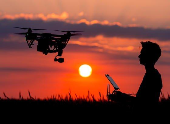 Sieht idylisch aus: Ein Junge sitzt auf einem Feld in Brandenburg und steuert bei Sonnenuntergang eine Drohne. Doch wie sollen kommerzielle Flüge mit Lieferdrohnen gesetzlich geregelt werden. Wie kann Sicherheit garantiert werden, wenn der Pilot das Fluggerät nicht mehr sehen kann? Und mehrere Drohnen gleichzeitig steuert? Amazon testet jetzt in Großbritannien solche Flüge.