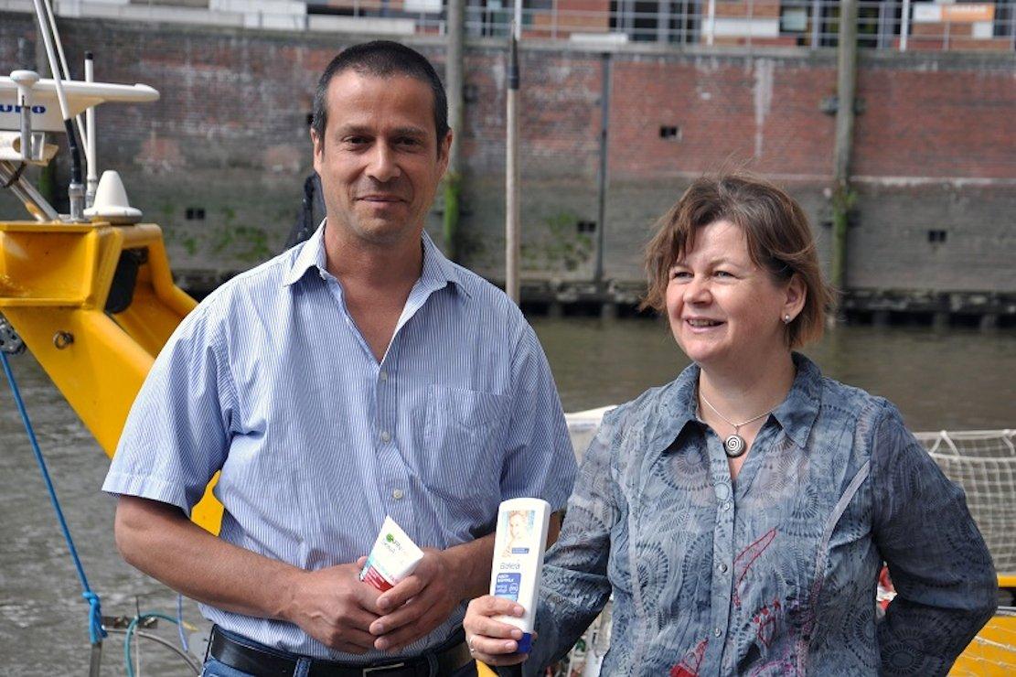 Der Diplom-Biologe Frank Schweikert und Prof. Gesine Witt halten Kosmetikprodukte und Shampoos in der Hand, die Mikroplastik enthalten. Das reichert sich stark im Sediment der Flüsse an.