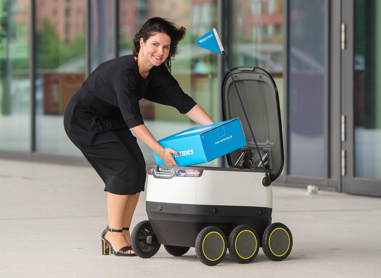Daniela Kirchner von dem Paketlieferanten Hermes belädt in Hamburg einen von der Firma Starships Technologies entwickelten Roboter.