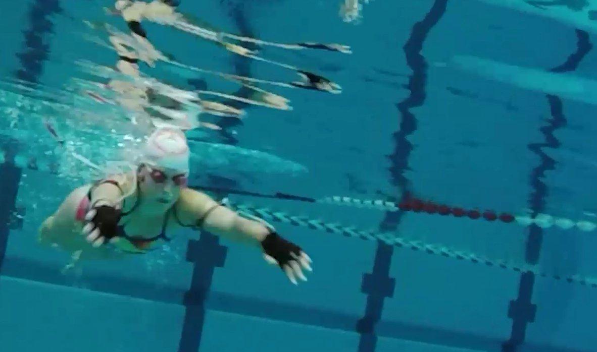 Schwimmerin mit Sensorhandschuhen. Eine Software wandelt die Strömungsdaten in Klänge um. Beim Training lassen sich dann ganze Melodien erzeugen.