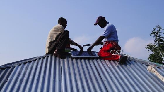 Solar-Moskitofalle: Montage der Solarpanel an einem Hausdach auf der Insel Rusinga in Kenya.