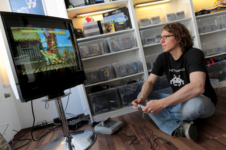 Der Inhaber eines Ladens für Retrospiele, Christoph Noll sitzt am 5. August 2016 in Köln vor einer Nintendo-Konsole. Viele Spiele auf der diesjährigen Gamescom brillieren mit opulenter Grafik. Aber die Szene kennt auch einen anderen Trend:die Sehnsucht nach Pixel-Look und den alten Lieblingskonsolen.