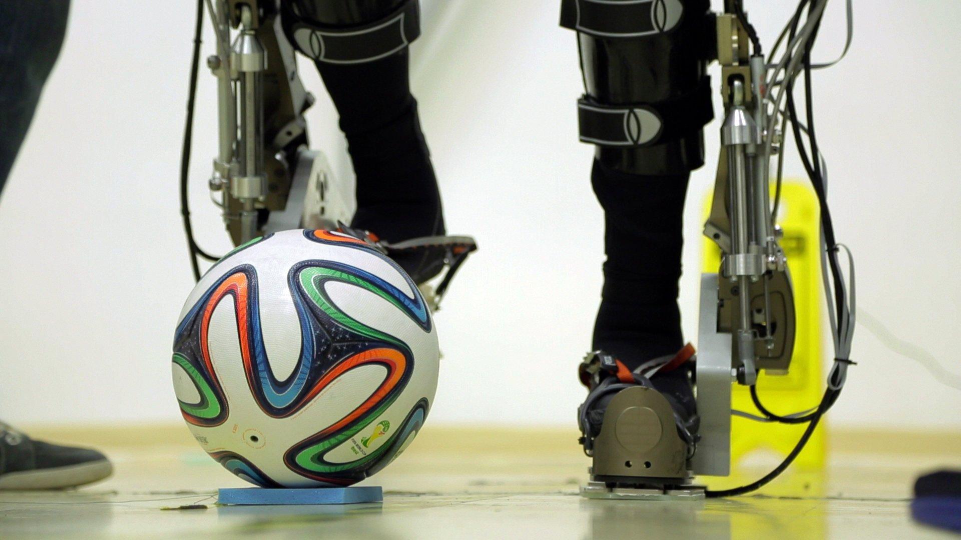 Eine Testperson kickt mit einem Spezial-Roboteranzug gegen den WM-Ball Brazuca. Der symbolische Anstoß zur Fußball-WM in São Paulo am 12. Juni 2014 war eine ganz besondere Premiere für einen brasilianischen Rollstuhlfahrer. Der querschnittgelähmte Patient schoss den Ball mit Hilfe eines Exoskeletts vom Spielfeldrand auf das Feld. Die Demonstration war Teil des internationalen Projektes Walk Again, an dem 156 Forscher, Ingenieure und Techniker unter Regie des brasilianischen Neurowissenschaftlers Miguel Nicolelis beteiligt sind.