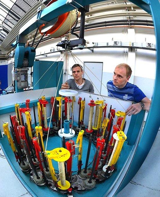 Ingo Berbig (l.) und Dirk Fischer bereiten an einer Flechtmaschine die Herstellung der textilen Speichen aus Hightech-Fasern vor.