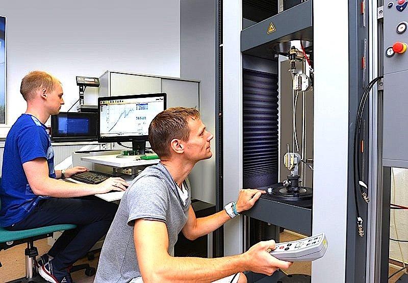 Dirk Fischer (l.) und Ingo Berbig von der TU Chemnitz bereiten an einer Prüfmaschine den Zugversuch eines Hightech-Faserseils vor.