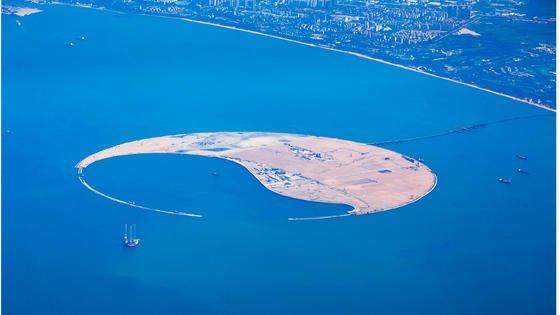 Diese künstliche Insel direkt vor der Küste der StadtHaikou soll in den nächsten Jahren zu einem Touristenparadies im Meer gestaltet werden.