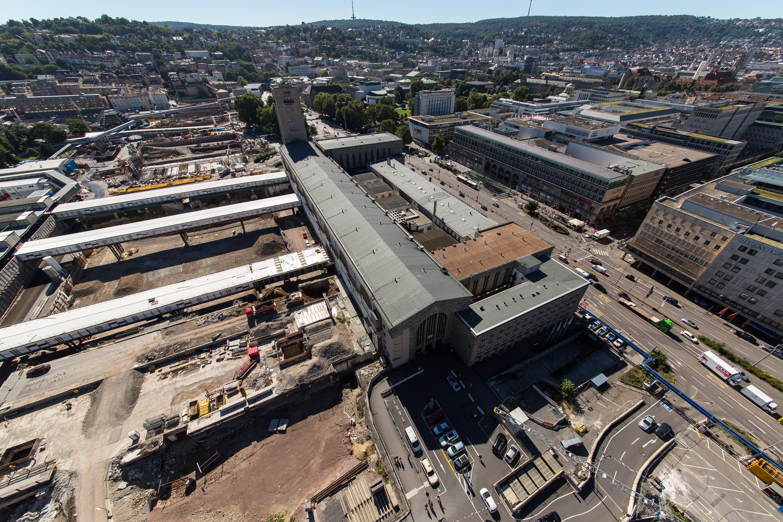 Die Baustelle des Tiefbahnhofs Stuttgart 21 im August aus der Luft gesehen: Das alte Bahnhofsgebäude rechts hat keinen direkten Gleisanschluss mehr. Die Gleise des Kopfbahnhofes, die früher bis zum Hauptgebäude reichten, enden schon seit Jahren weit vor dem Bahnhof.