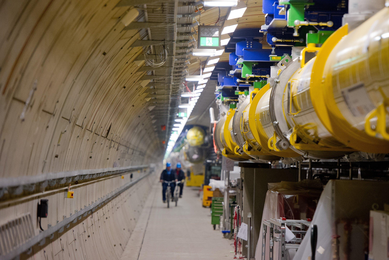 Mitarbeiter fahren in Hamburg im Teilchenbeschleuniger-Tunnel des Röntgenlasers European XFEL am Beschleuniger (gelb) entlang.