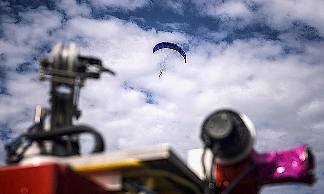 Über eine Winde sind zwei Drachen miteinander verbunden.Während der eine Schirm in bis zu 450 m Höhe aufsteigt, sinkt der andere herab.