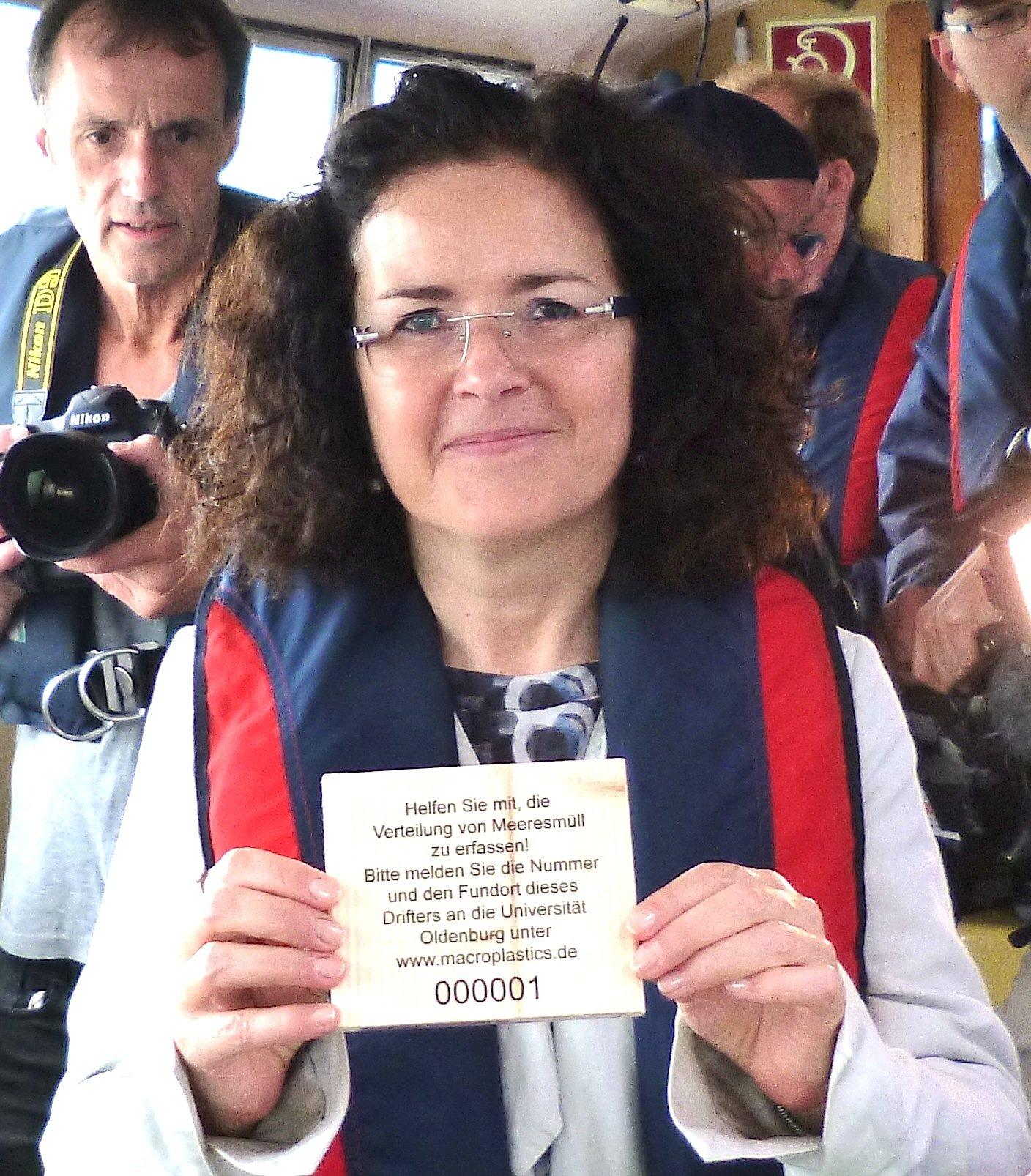 Die niedersächsische Wissenschaftsministerin Gabriele Heinen-Kljajić hält ein Holztäfelchen in der Hand. 100.000 werden in der Nordsee verteilt.