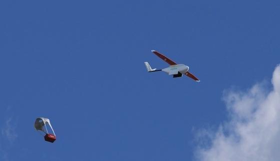 Drohne von Zipline: Der unbemannte Flieger wirft Blutkonserven ab, die am Fallschirm zu Boden segeln. Das geht schneller als ein Lkw-Transport.