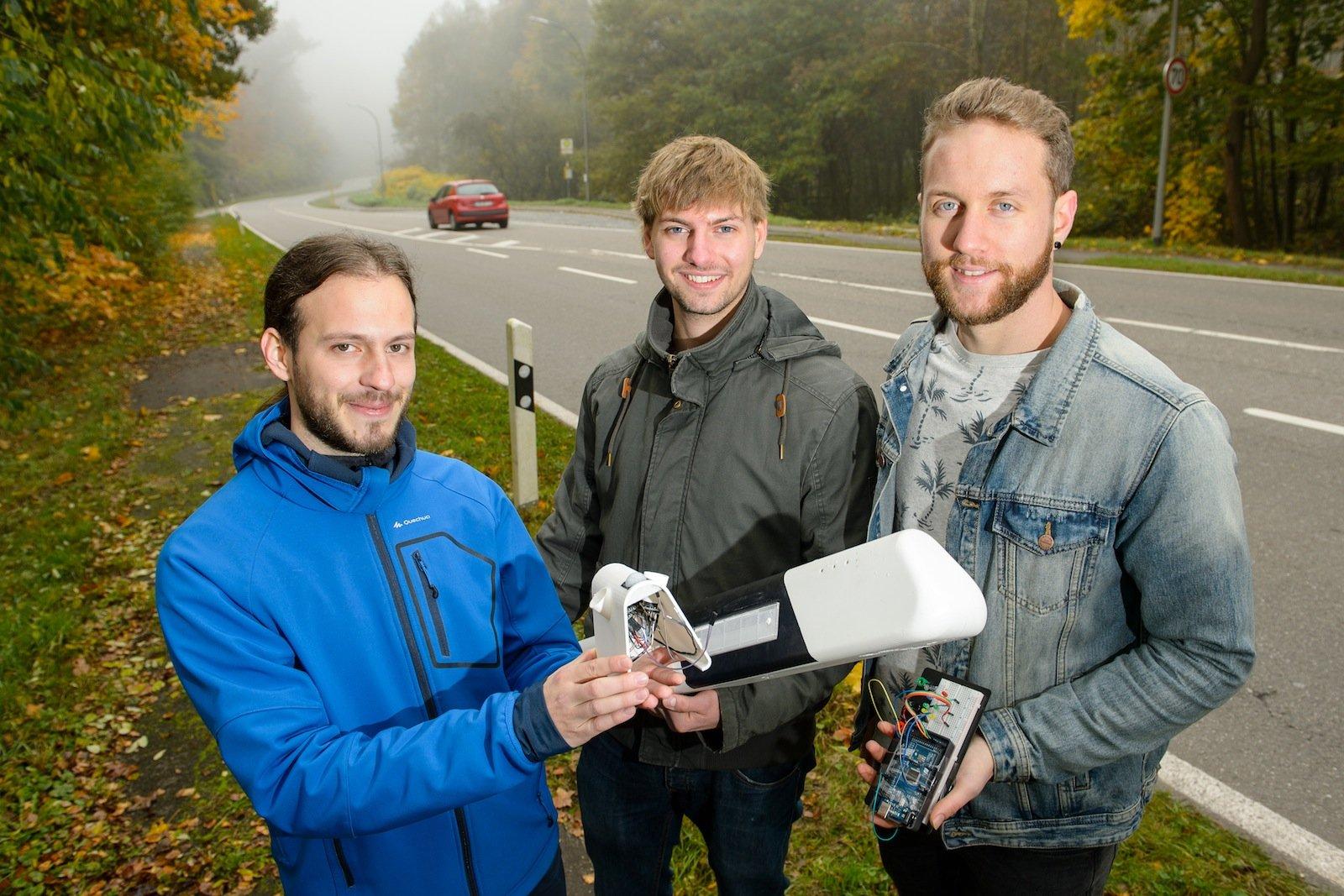 Der Prototyp, den die angehenden Ingenieure Benjamin Kirsch (li.), Daniel Gillo (Mitte) und Julian Neu (re.) an der Saar-Universität gebaut haben, wird im oberen Teil eines Leitpfostens installiert.