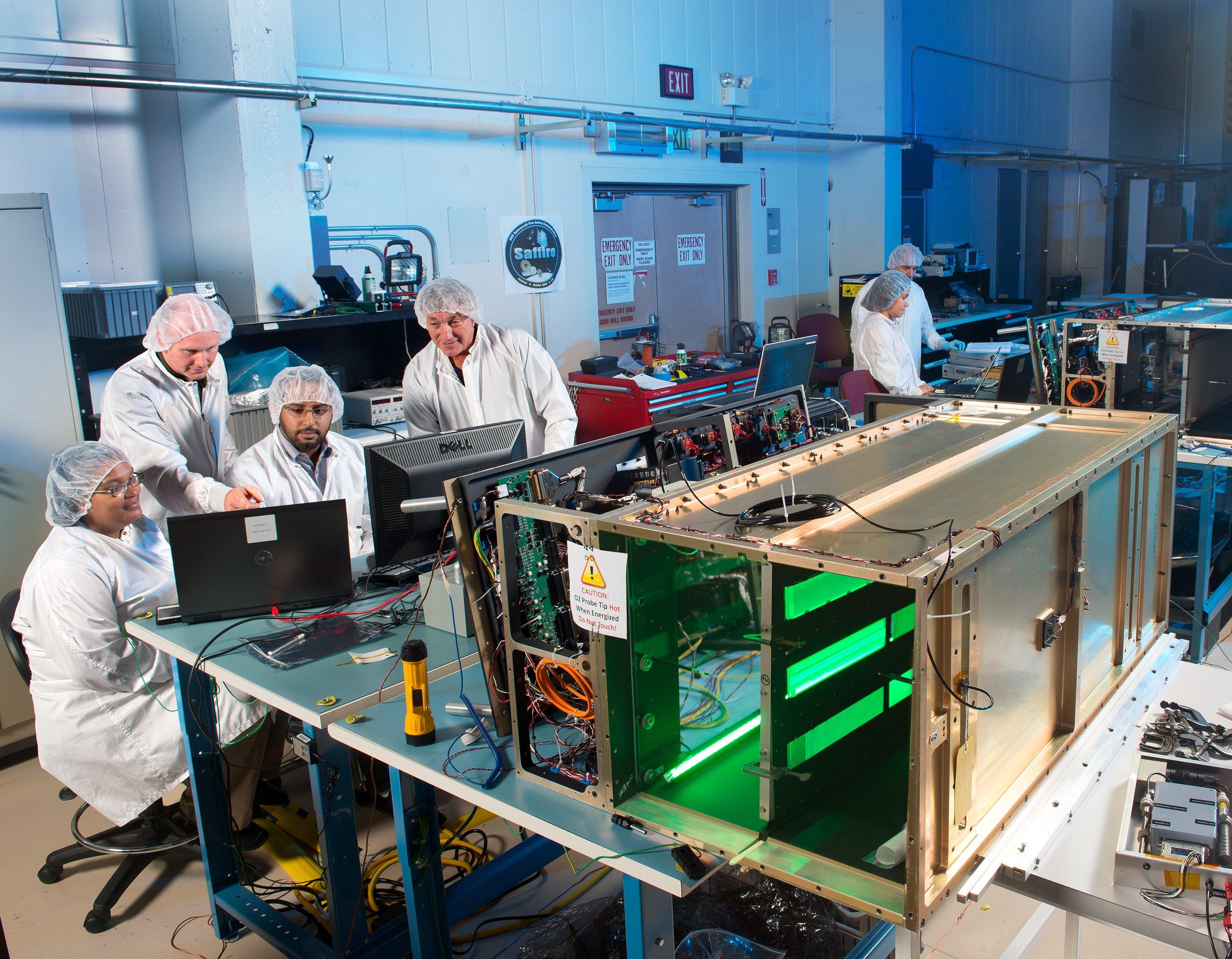 Ein Ingenieursteam des Nasa Glenn Research Centers in Cleveland bei Tests am Saffire II-Experiment. Die mittlere der drei sichtbaren, grün leuchtenden Proben ist die des Zarm. Die obere Probe ist ebenfalls aus Acrylglas, hat die gleichen Abmessungen jedoch ohne Strukturen und dient als Referenzexperiment.