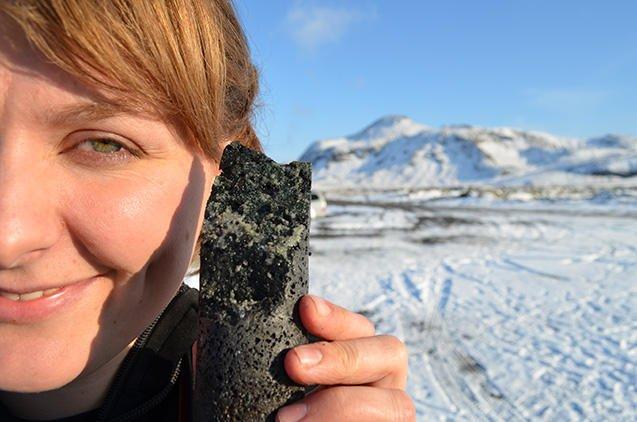 Forscherin Sandra Snaebjornsdottir zeigt einen Basaltstein, in dem CO2 zu Karbonat (weiß) mineralisiert ist. Die Umwandlung dauert weniger als zwei Jahre, nicht wie bislang angenommen hunderte bis tausende von Jahren.