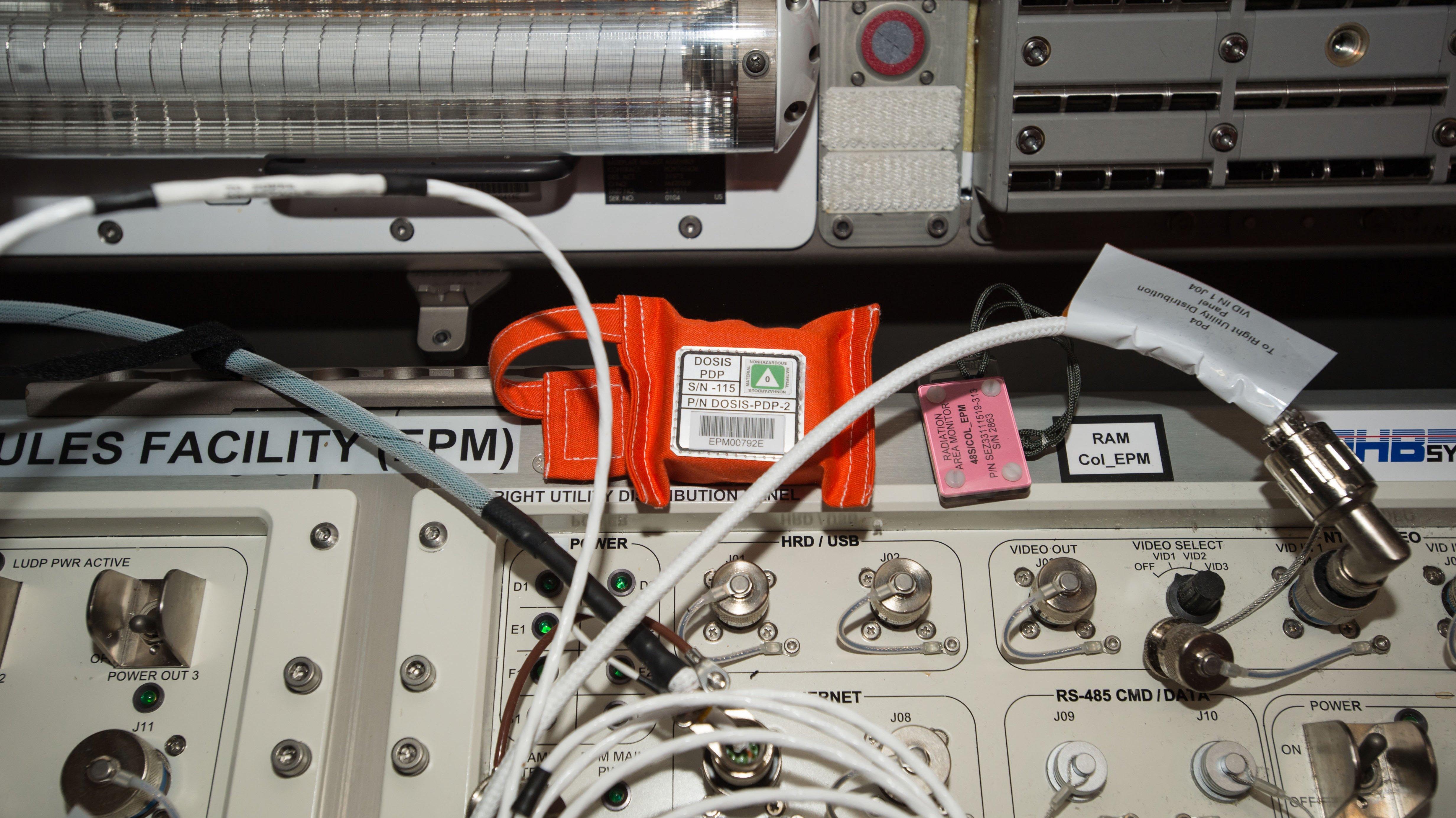 Im Inneren des orangenen Päckchens befinden sich hunderte von kleinen Detektoren, die im Forschungslabor Columbus der ISS die Strahlung erfassen. 11 solcher Detektoren-Sets sind jetzt installiert und messen sechs Monate lang die Belastung durch kosmische Strahlung. Das Deutsche Zentrum für Luft- und Raumfahrt (DLR) leitet das Experiment Dosis 3D.