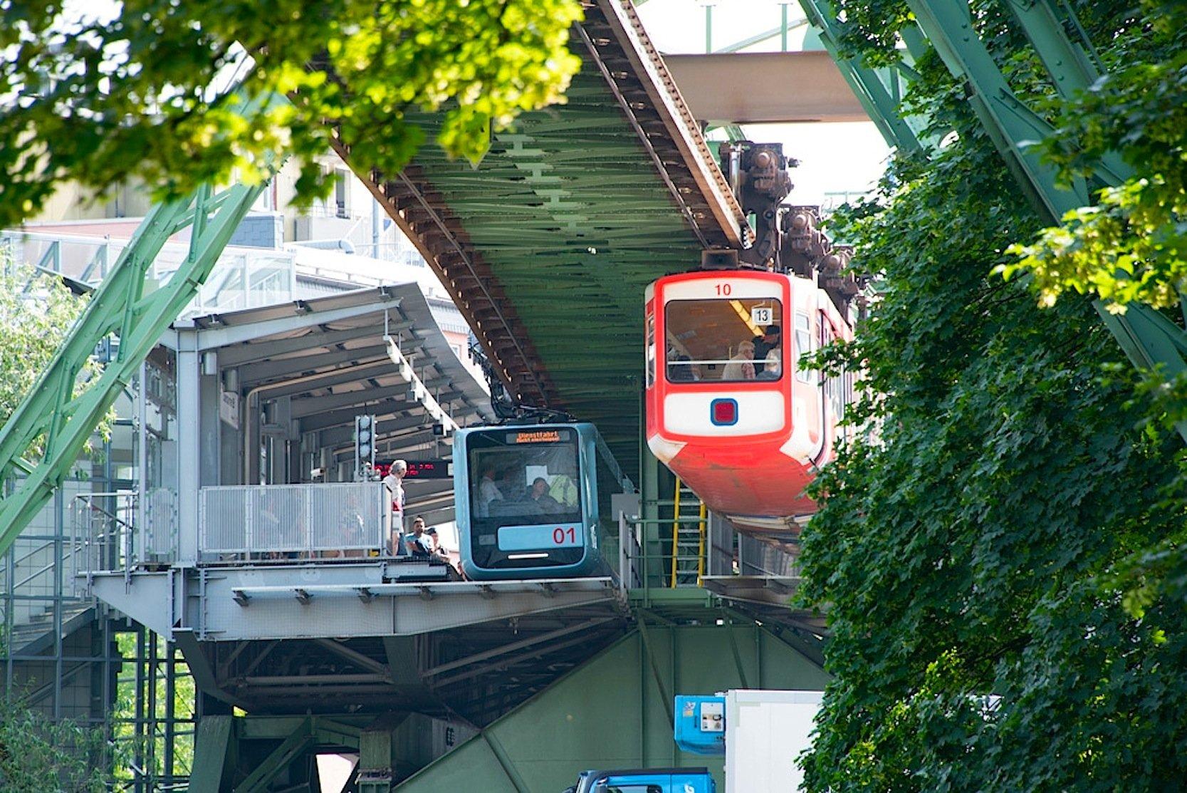 Links die neue blaue Schwebebahn, rechts eine 40 Jahre alte Bahn in orange.