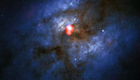 Dieses Kompositbild zeigt eine neue Alma-Band-5-Aufnahme des kollidierenden Galaxiesystems Arp 220 (in rot) über einem Bild des Hubble-Weltraumteleskops(blau/grün). Mit den neu installierten Band-5-Empfängern blickt Alma auf einen ganz neuen Teil dieses Radiospektrums und verbessert die Möglichkeit des Teleskops im Universum nach Wasser zu suchen. Dieses Bild ist eines der ersten, beim dem das Band 5 verwendet wurde.
