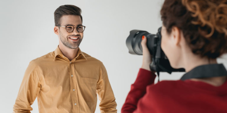Mann mit gelbem Hemd steht vor einer Fotografin und lächelt