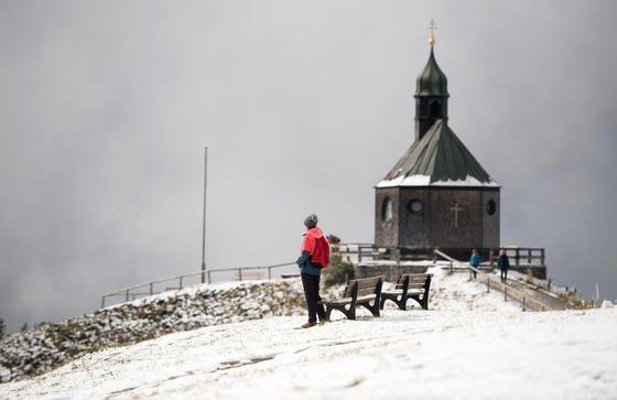 Wanderer im Schnee an der Wallbergkapelle am Tegernsee: Auch im Herbst und Winter sollte man sich viel Licht und frische Luft gönnen, um gegen den Winterblues anzugehen.