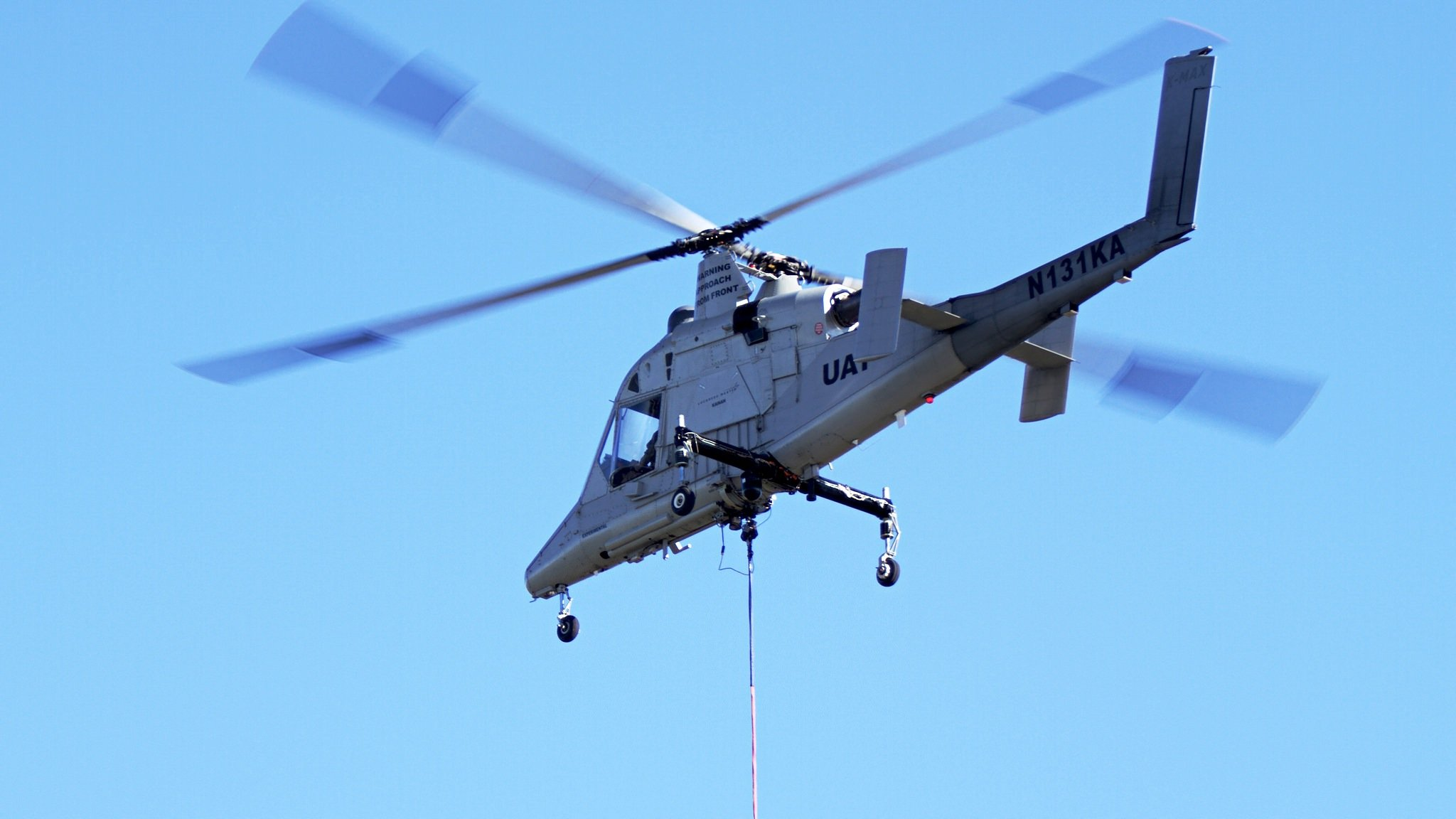 Der Hubschrauber des Typs Kaman K-Max fliegt ebenfalls ohne Pilot und kann große Lasten transportieren, beispielsweise Löschwasser.