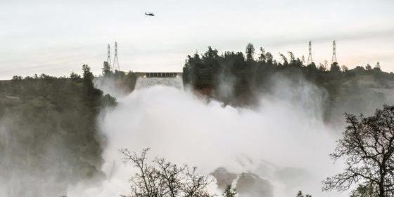 Ein Hubschrauber transportiert am 13. Februar 2017 in Oroville (USA) einen Behälter mit Felsen, um den beschädigten Überlauf des Oroville-Staudamms zu sichern. 200.000 Menschen mussten evakuiert werden, weil der Damm infolge starker Niederschläge zu brechen drohte.