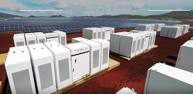 Im Vordergrund sind die weißen Powerpacks von Tesla zu sehen, in denen der Sonnenstrom zwischengespeichert wird.