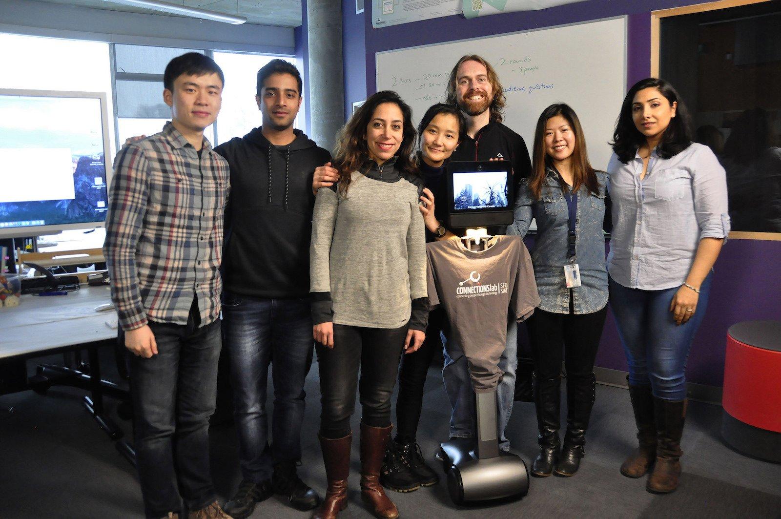 Prof. Carman Neustaedter (3.v.r.) und sein Team mit einem der Telepräsenzroboter.