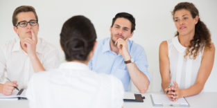 Drei Personen im Business-Kontext sitzen einer Frau gegenüber