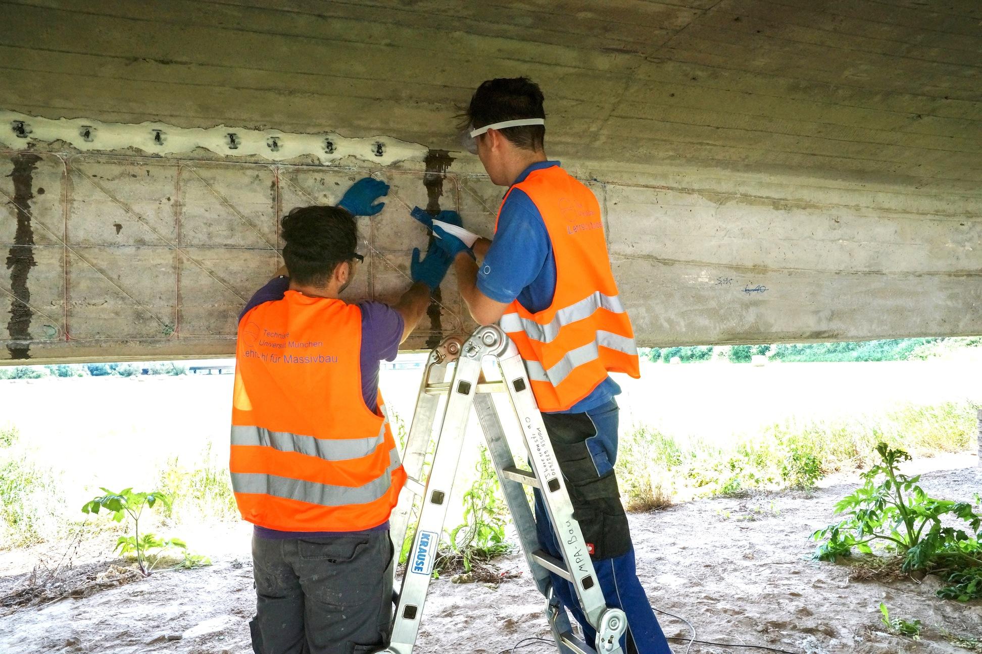 Das Messteam der TU München beim Aufkleben der faseroptischen Sensoren auf den Beton der Saalebrücke. Anschließend wird die Brücke der Last schwerer Laster ausgesetzt, die Sensoren messen dann die Änderungen im Beton.