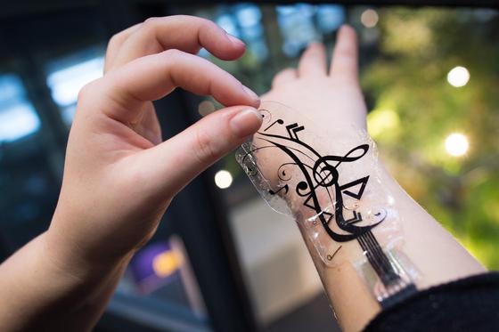 Diese Sensorfolie lässt sich mit einem biomedizinischen Kleber auf der Haut befestigen. Über die einzelnen Symbole lassen sich Funktionen von Smartphone oder MP3-Player steuern – etwa Lautstärke oder die Mute-Funktion.