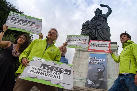 """Aktivisten vom BUND Naturschutz in Bayern demonstrieren am 2. August 2017 mit einem großem Plakat mit der Aufschrift """"Mir stinkts! Saubere Luft für Bavaria"""" unterhalb der Bavaria-Statue an der Theresienwiese in München. Die Aktion fand gleichzeitig mit dem Diesel-Gipfel in Berlin statt."""