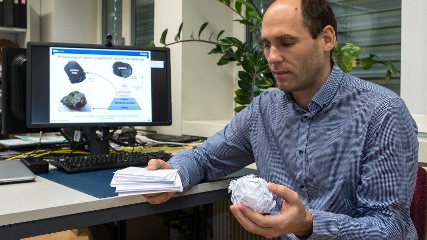 Konstiantyn Kravchyk hat Papier zerknüllt, um die Struktur von Graphit zu demonstrieren. Der Stapel Papier soll das Abfall-Graphit zeigen, das zerknüllte Papier den vermahlenen Rohstoff.
