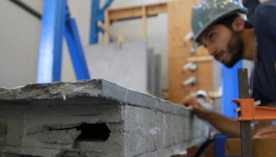 Forscher Salman Soleimani inspiziert die EDCC-verstärkte Wand nach dem Erdbebensimulationstest.