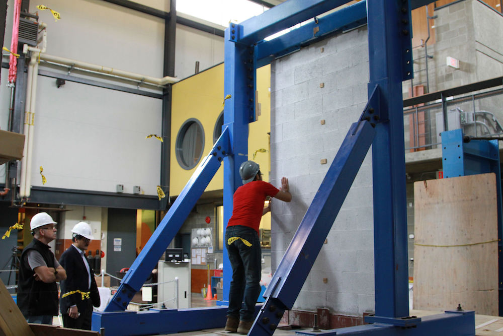 Die EDCC-verstärkte Wand wird zwischen Erdbebensimulationstests auf Risse und Schäden untersucht.