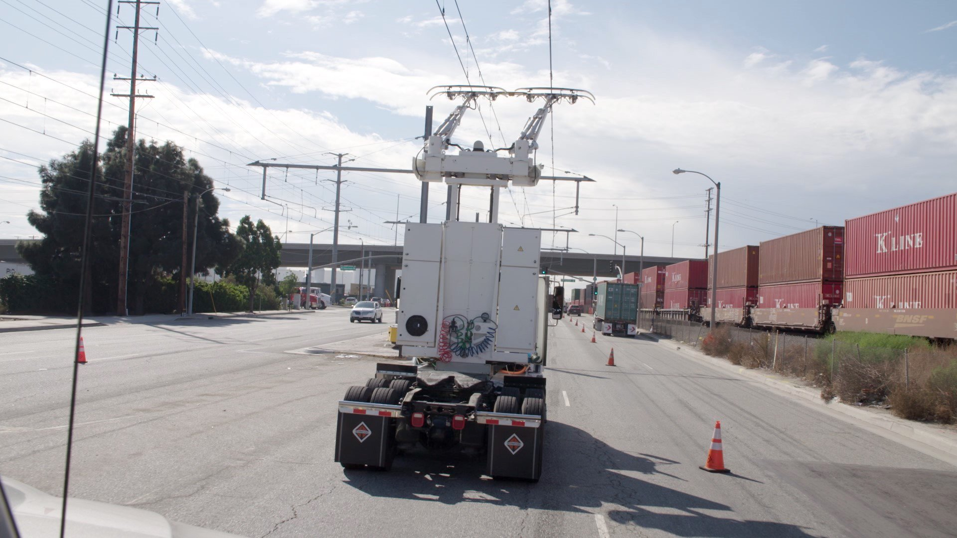Die Strommasten stehen auf der Mittelspur, um beide Fahrbahnen zu überragen. Verlassen die Lkw die Teststrecke, klappen sie den Stromabnehmer ein und fahren mit dem Verbrennungsmotor weiter.
