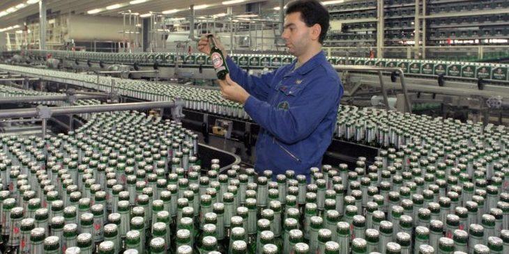 Ein Brauereimitarbeiter hält in der Abfüllanlage eine Flasche prüfend in den Händen.